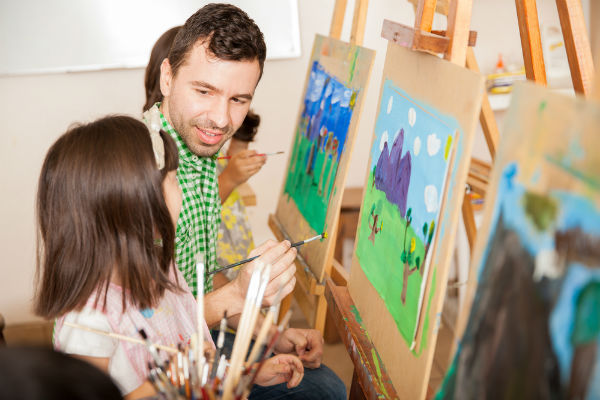 hombre-enseñando-pintura-niños